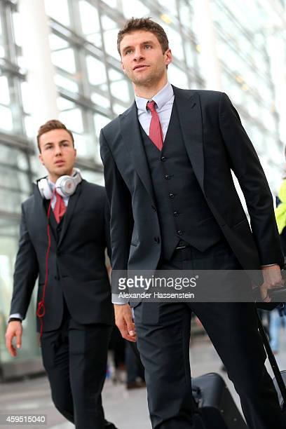 Thomas Mueller of FC Bayern Muenchen and his team mate Mario Goetze arrive with the team at Munich Airport to depart for their UEFA Champions League...