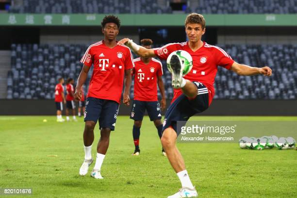 Thomas Mueller of FC Bayern Muenchen battles for the ball with his team mate David Alaba during a training session at Shenzhen Universiade Sports...