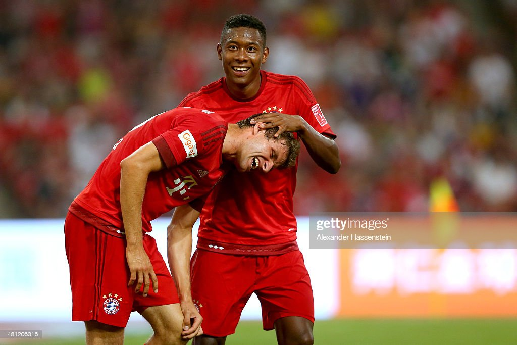 Thomas Mueller of FC Bayern Muenchen celebrates a score with his team mate David Alaba (R) during the international friendly match between FC Bayern Muenchen and Valencia FC during the Audi Football Summit Beijing 2015 at National Stadium on July 18, 2015 in Beijing, China.