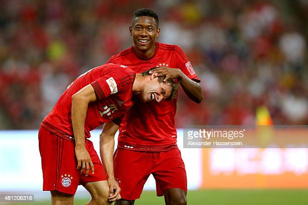 Thomas Mueller of FC Bayern Muenchen celebrates a score with his team mate David Alaba during the international friendly match between FC Bayern...