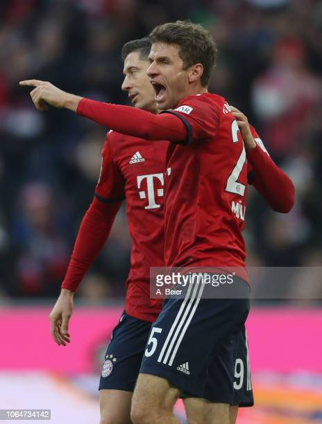 Thomas Mueller of FC Bayern Muenchen celebrates his first goal with teammate Robert Lewandowski during the Bundesliga match between FC Bayern...