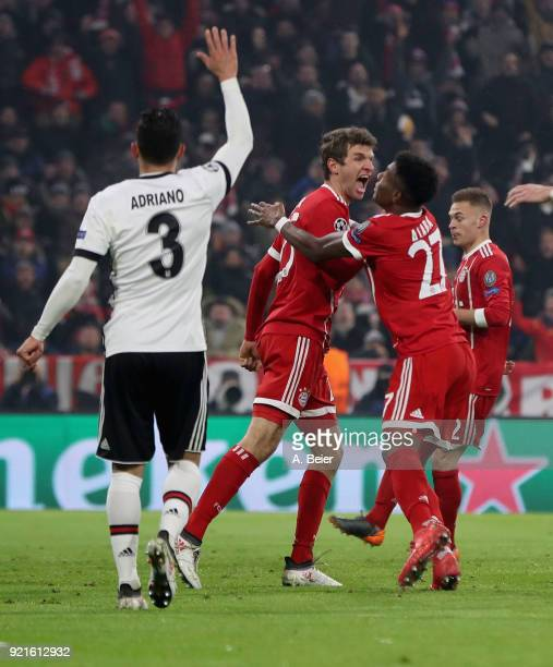 Thomas Mueller of FC Bayern Muenchen celebrates his first goal with teammate David Alaba during the UEFA Champions League Round of 16 first leg match...