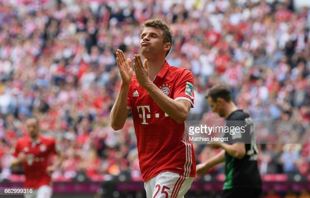 Thomas Mueller of FC Bayern Muenchen celebrates with his teammates after scoring his team's second goal during the Bundesliga match between Bayern...