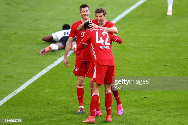 Thomas Mueller of FC Bayern Muenchen celebrates with Robert Lewandowski and Jamal Musiala after scoring their side's second goal during the...