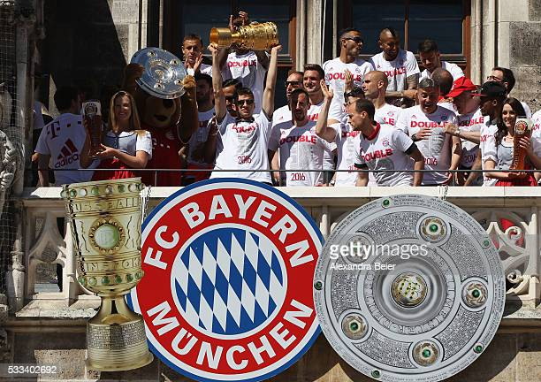 Thomas Mueller of FC Bayern Muenchen celebrates with the trophy the team's German Cup and German Championship victory on the town hall balcony at...