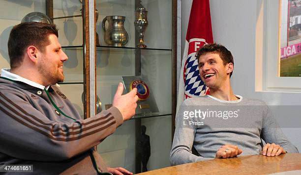 Thomas Mueller of FC Bayern Muenchen chats with a fan during a Meet Greet with fans on February 24 2014 in Munich Germany