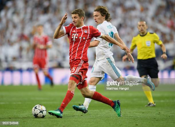 Thomas Mueller of FC Bayern Muenchen is challenged by Luka Modric of Real Madrid during the UEFA Champions League Semi Final Second Leg match between...