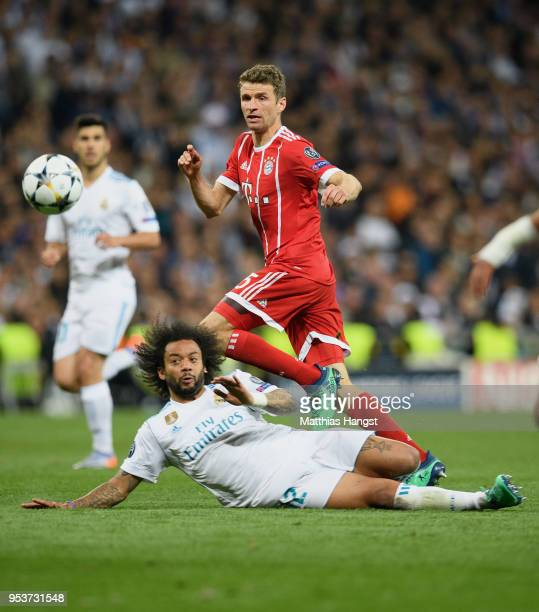 Thomas Mueller of FC Bayern Muenchen is challenged by Marcelo of Real Madrid during the UEFA Champions League Semi Final Second Leg match between...