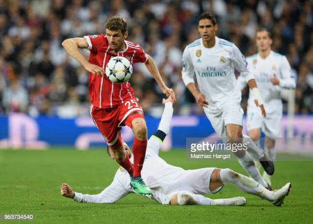 Thomas Mueller of FC Bayern Muenchen is challenged by Sergio Ramos of Real Madrid during the UEFA Champions League Semi Final Second Leg match...