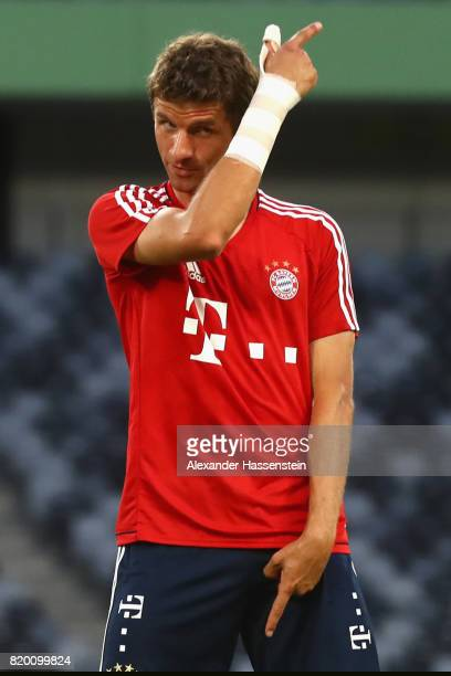 Thomas Mueller of FC Bayern Muenchen jokes with his team mates during a training session at Shenzhen Universiade Sports Centre during the Audi Summer...