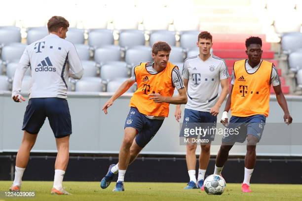 Thomas Mueller of FC Bayern Muenchen plays the ball next to his teammates Benjamin Pavard and Alphonso Davies during a training session at Allianz...