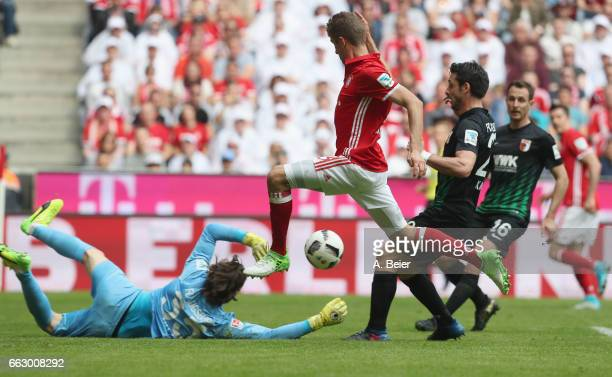 Thomas Mueller of FC Bayern Muenchen scores his first goal against goalkeeper Marwin Hitz and Gojko Kacar of FC Augsburg during the Bundesliga match...