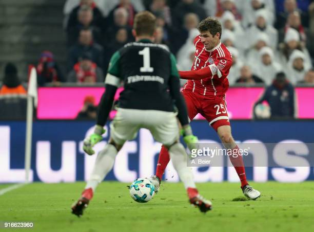 Thomas Mueller of FC Bayern Muenchen scores his first goal against goalkeeper Ralf Faehrmann of FC Schalke 04 during the Bundesliga match between FC...