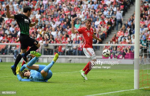 Thomas Mueller of FC Bayern Muenchen scores his team's second goal past goalkeeper Marwin Hitz of Augsburg during the Bundesliga match between Bayern...