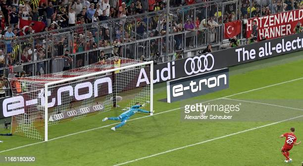 Thomas Mueller of FC Bayern Muenchen scores his team's third goal against goakeeper Harun Tekin of Fenerbahce during the Audi cup 2019 semi final...