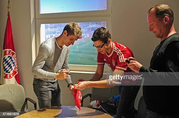 Thomas Mueller of FC Bayern Muenchen sings jerseys of fans during a Meet Greet with fans on February 24 2014 in Munich Germany