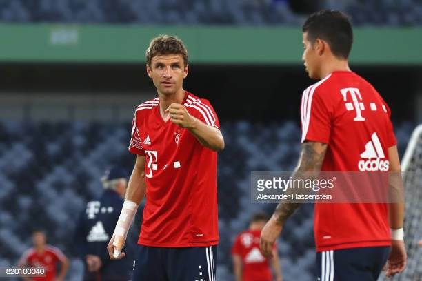 Thomas Mueller of FC Bayern Muenchen talks to his team mate James Rodriguez during a training session at Shenzhen Universiade Sports Centre during...