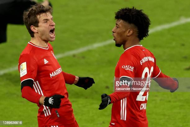 Thomas Mueller of FC Bayern Munich celebrates with teammate Kingsley Coman after scoring his team's second goal during the Bundesliga match between...