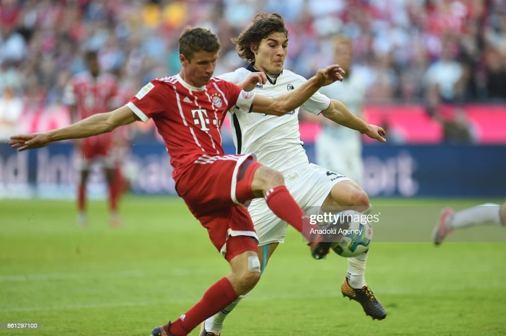 Thomas Mueller (L) of FC Bayern Munich in action against Caglar Soyuncu (R) of SC Freiburg during the Bundesliga soccer match between FC Bayern Munich and SC Freiburg at Allianz Arena in Munich, Germany on October 14, 2017.