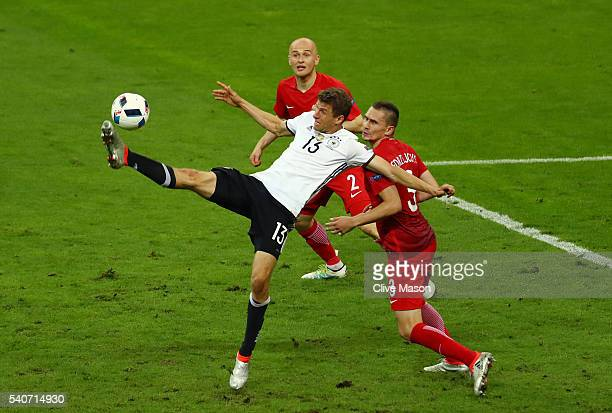 Thomas Mueller of Germany and Artur Jedrzejczyk of Poland compete for the ball during the UEFA EURO 2016 Group C match between Germany and Poland at...