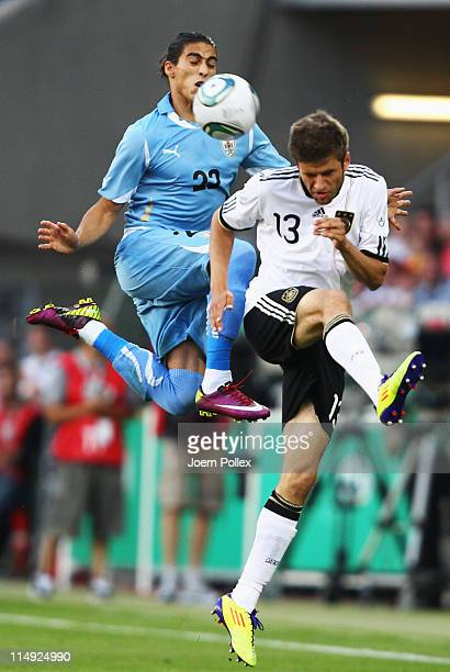 Thomas Mueller of Germany and Martin Caceres of Uruguay battle for the ball during the international charity match between Germany and Uruguay at...