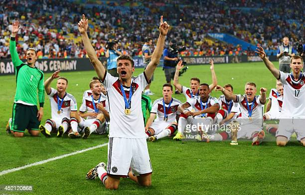 Thomas Mueller of Germany and teammates celebrate with the World Cup trophy after defeating Argentina 10 in extra time during the 2014 FIFA World Cup...
