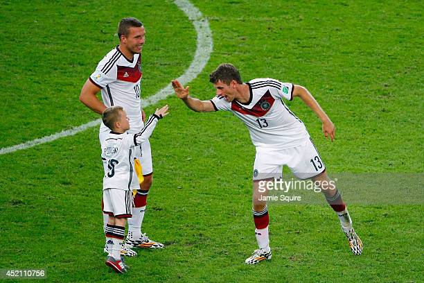 Thomas Mueller of Germany celebrates defeating Argentina 10 in extra time with Lukas Podolski and his son Louis Podolski during the 2014 FIFA World...