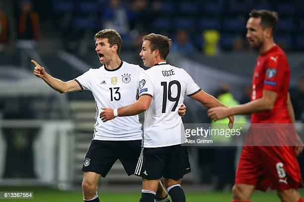 Thomas Mueller of Germany celebrates his team's first goal with team mate Mario Goetze during the FIFA World Cup 2018 qualifying match between...