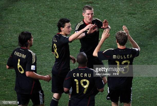 Thomas Mueller of Germany celebrates scoring his side's first goal with team mates Sami Khedira Mesut Oezil Cacau and Bastian Schweinsteiger during...