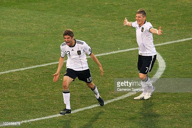 Thomas Mueller of Germany celebrates scoring his side's third goal with team mate Bastian Schweinsteiger during the 2010 FIFA World Cup South Africa...
