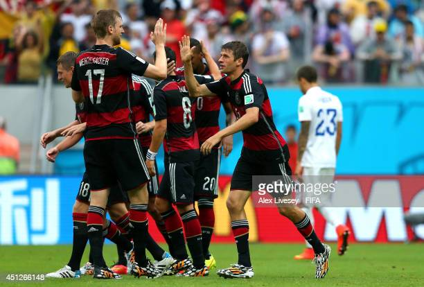 Thomas Mueller of Germany celebrates scoring his team's first goal with his teammates during the 2014 FIFA World Cup Brazil Group G match between USA...
