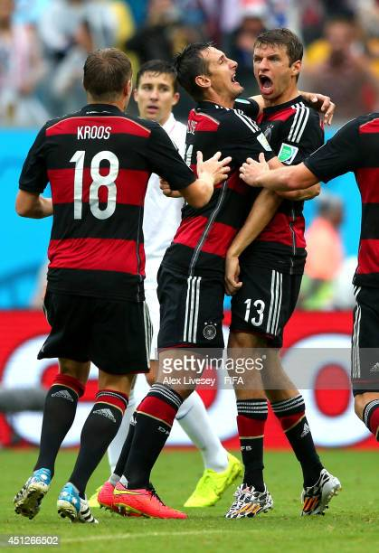 Thomas Mueller of Germany celebrates scoring his team's first goal with his teammates Miroslav Klose and Toni Kroos during the 2014 FIFA World Cup...