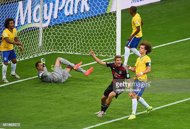Thomas Mueller of Germany celebrates scoring his team's first goal past Julio Cesar of Brazil during the 2014 FIFA World Cup Brazil Semi Final match...