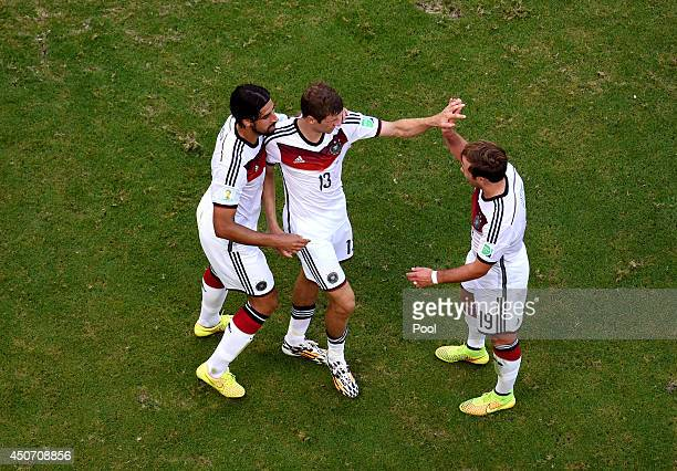 Thomas Mueller of Germany celebrates scoring his team's third goal with teammates Sami Khedira and Mario Goetze during the 2014 FIFA World Cup Brazil...