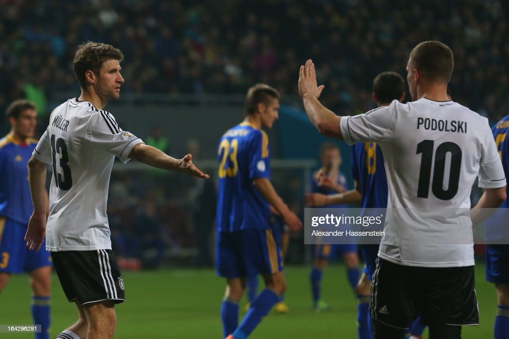 Thomas Mueller (L) of Germany celebrates scoring the 4th team goal with his team mate Lukas Podolski during the FIFA 2014 World Cup qualifier group C match between Kazakhstan and Germany at Astana Arena on March 22, 2013 in Astana, Kazakhstan.