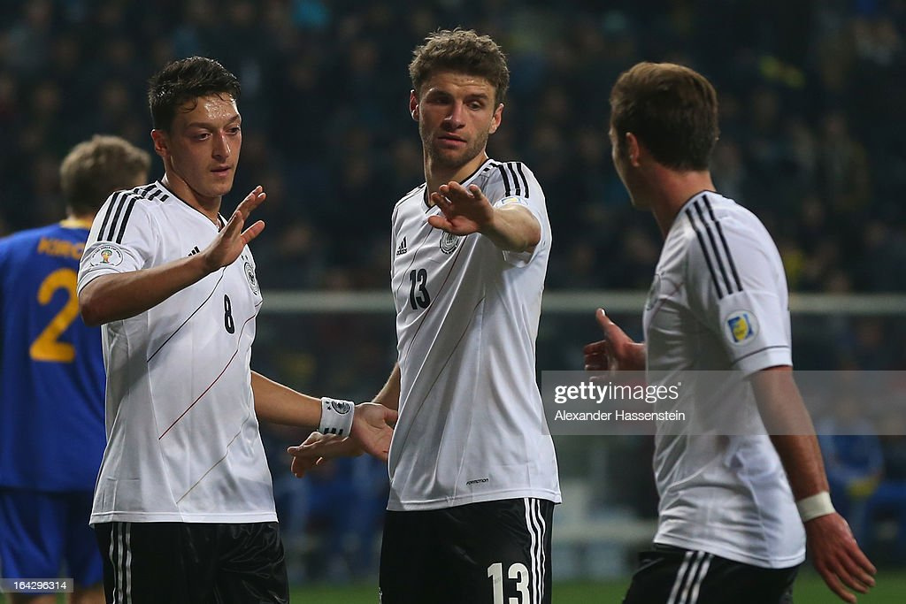 Thomas Mueller (C) of Germany celebrates scoring the 4th team goal with his team mates Mesut Oezil (L) and Mario Goetze (R) during the FIFA 2014 World Cup qualifier group C match between Kazakhstan and Germany at Astana Arena on March 22, 2013 in Astana, Kazakhstan.