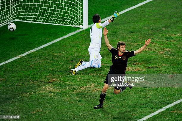 Thomas Mueller of Germany celebrates scoring the opening goal past Fernando Muslera of Uruguay during the 2010 FIFA World Cup South Africa Third...