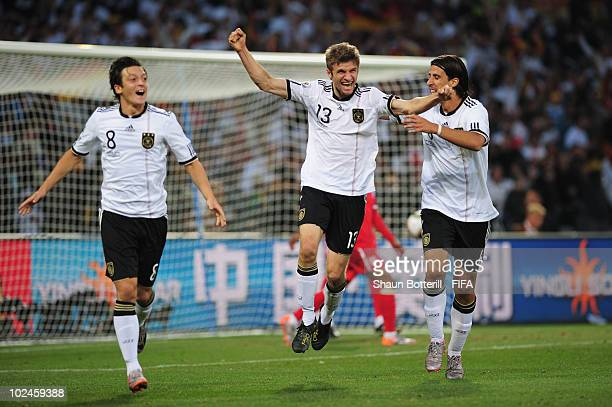 Thomas Mueller of Germany celebrates scoring their fourth goal with teammates Sami Khedira and Mesut Oezil during the 2010 FIFA World Cup South...