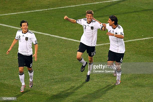 Thomas Mueller of Germany celebrates scoring with team mates Mesut Oezil and Sami Khedira during the 2010 FIFA World Cup South Africa Round of...