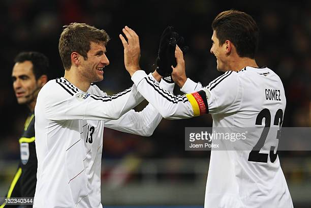 Thomas Mueller of Germany celebrates with his team mate Mario Gomez after scoring his team's third goal during the International Friendly match...