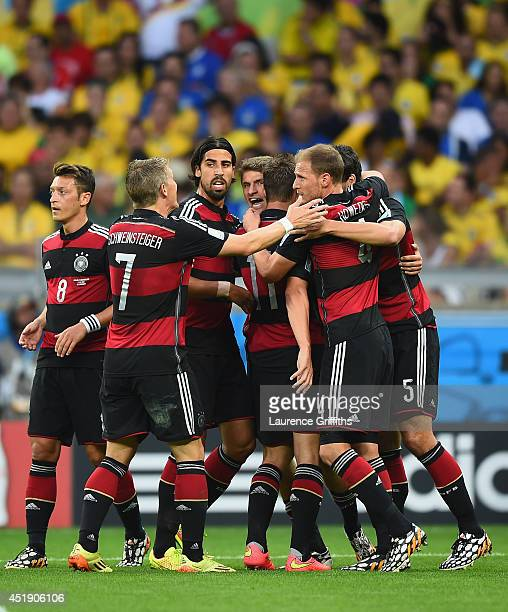 Thomas Mueller of Germany celebrates with his team-mates after scoring the opening goal during the 2014 FIFA World Cup Brazil Semi Final match...