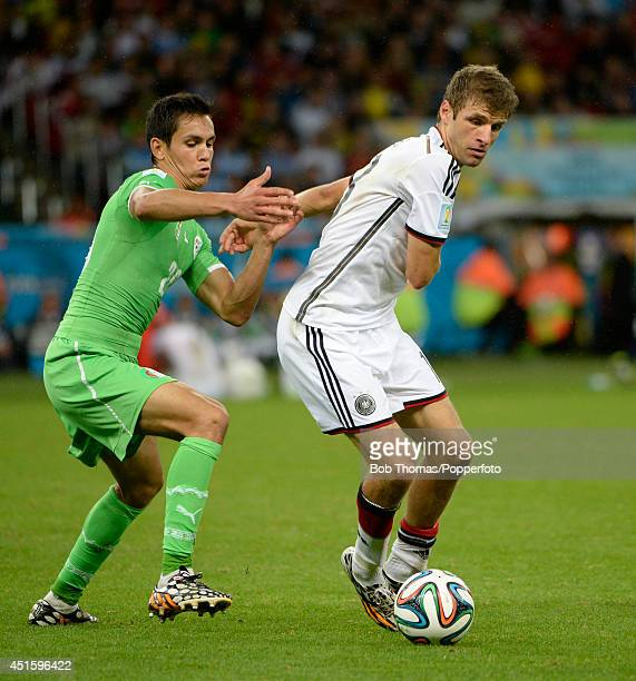 Thomas Mueller of Germany challenged by Aissa Mandi of Algeria during the 2014 FIFA World Cup Brazil Round of 16 match between Germany and Algeria at...