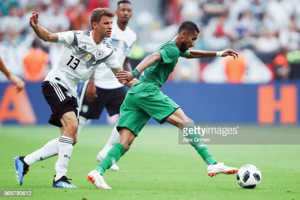 Thomas Mueller of Germany holds Salman AlFaraj of Saudi Arabia during the international friendly match between Germany and Saudi Arabia ahead of the...