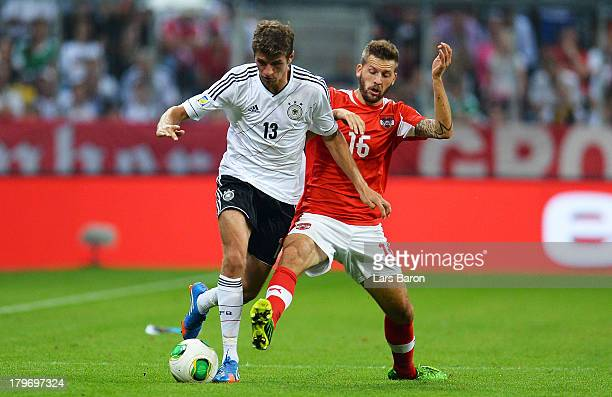 Thomas Mueller of Germany is challenged by Guido Burgstaller of Austria during the FIFA 2014 World Cup Qualifying Group C match between Germany and...