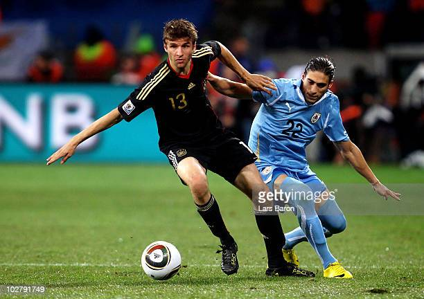 Thomas Mueller of Germany is challenged by Martin Caceres of Uruguay during the 2010 FIFA World Cup South Africa Third Place Playoff match between...