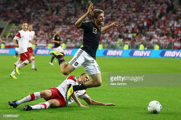 Thomas Mueller of Germany is fouled for a penalty by Arkadiusz Glowacki of Poland during the International friendly match between Poland and Germany...