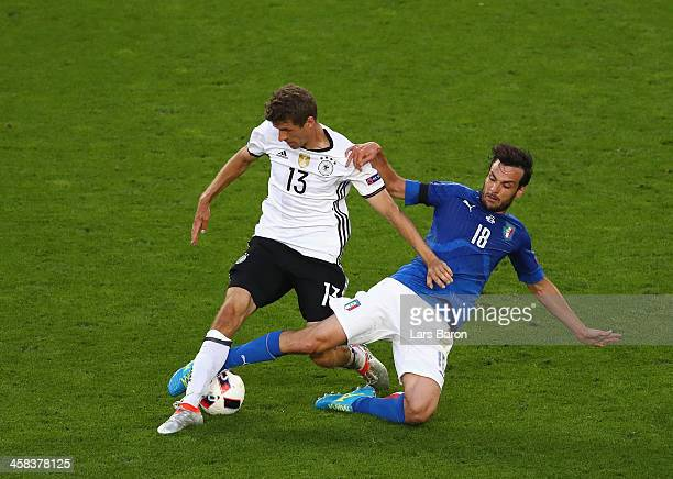 Thomas Mueller of Germany is tackled by Marco Parolo of Italy during the UEFA EURO 2016 quarter final match between Germany and Italy at Stade Matmut...