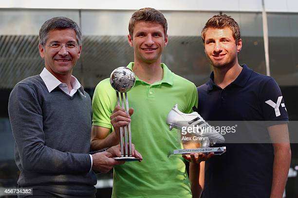 Thomas Mueller of Germany poses with CEO Herbert Hainer and his brother Simon Mueller after receiving the adidas Silver Ball and adidas Silver Shoe...