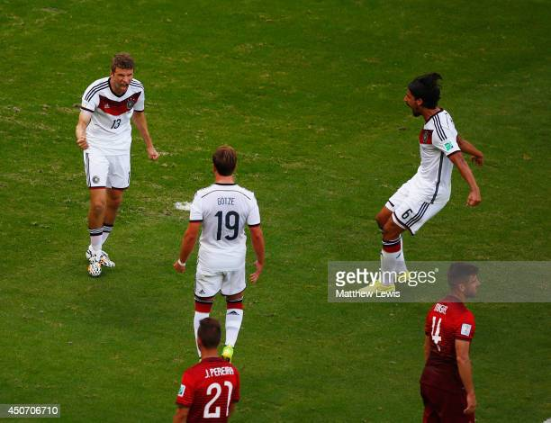 Thomas Mueller of Germany reacts after scoring his team's first goal on a penalty kick with Mario Goetze and Sami Khedira during the 2014 FIFA World...