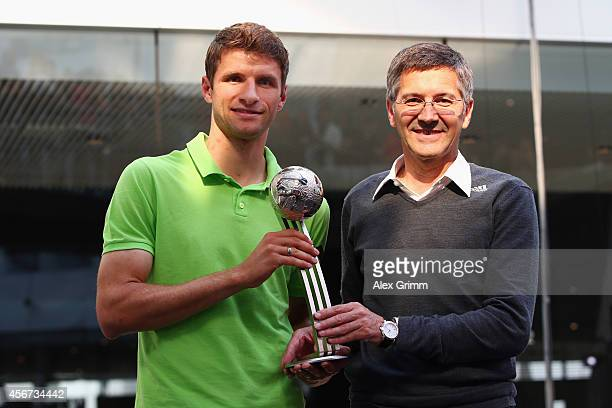 Thomas Mueller of Germany receives adidas Silver Ball award from adidas CEO Herbert Hainer during his visit at the adidas headquarters on October 6...